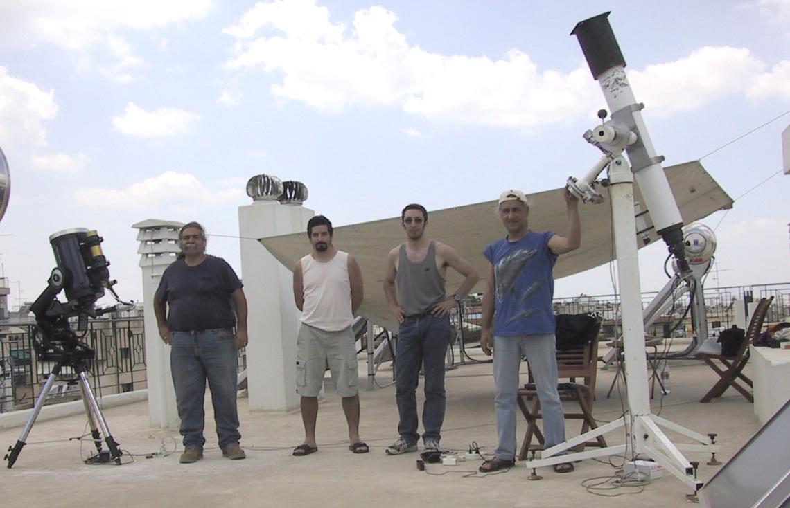 """Οι παρατηρητές (από αριστερά προς τα δεξιά): Ley Fred, Μαραβέλιας Γρηγόρης, Μπελιάς Γιάννης και Στέλλας Ιάκωβος. Μαζί φαίνονται τα τρία τηλεσκόπια που χρησιμοποιήθηκαν: 10"""" LX-200 Meade (Ηλιακό φίλτρο) με 60mm Coronado Maxscope και διοπτρικό 130mm F/10.8 (Ηλιακό φίλτρο)."""